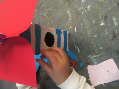 Een rood dak en een bijna abstract voederhuis ofwel vogelhuis door de blauwe lijnen