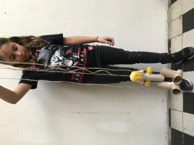 Marionet met lange touwen om de marionet te bewegen en met grote voeten rond te stappen.