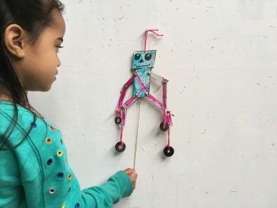 Trekpop die een robot voorspelt. De armen en benen kunnen bewegen door te trekken aan een touw.