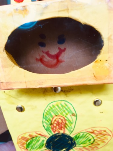 Dubbel gezichtje van de trekpop. Op de achterkant van het doosje en op het raampje is een gezichtje getekend.