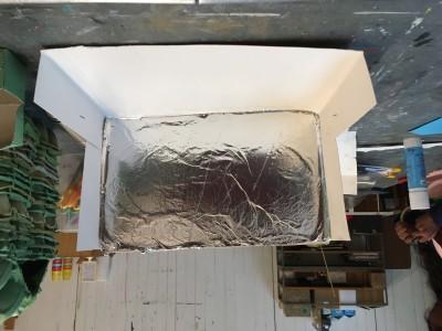 Spiegel, het begin van een kapperszaak. Driebanden van kartonnen de middelste wand bedekt met aluminiumfolie