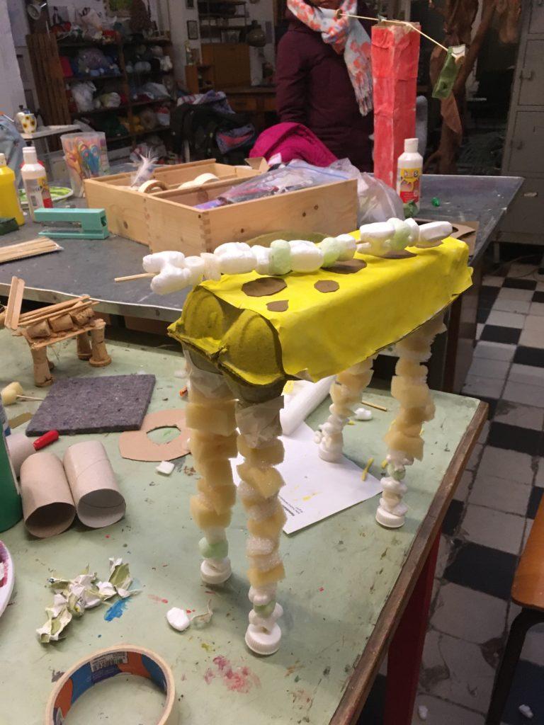 Giraffe. Een lege eierdoos dat wordt een buik. En de poten zijn satestokjes met schuimplastic