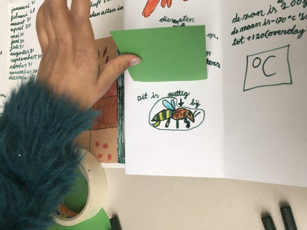 Het groene flapje is omhoog en daar verschijnt een bij. Want een bij maakt deel uit van de natuur en is heel nuttig