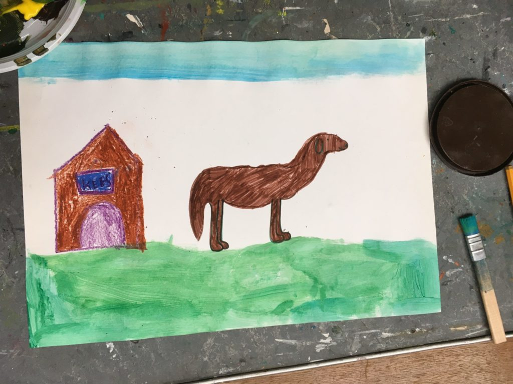 En toen was de tekening af met een hondenhok en de naam van de hond en groen gras en een blauwe hemel. Potlood, stift, wasco en verf